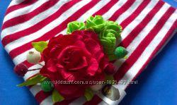 Шапка украшена цветами ручной работы.