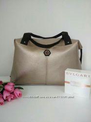 Стильная женская сумка с ремешками по бокам и эмблемой